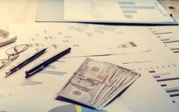 在书桌上的美元在与图表,笔,在桌上的玻璃的计划后 免版税库存图片