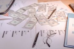 在书桌上的美元在与图表,笔,在桌上的玻璃的计划后 库存照片