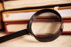 在书桌上的老放大镜 免版税库存照片