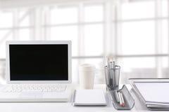 在书桌上的膝上型计算机在现代办公室 免版税库存照片