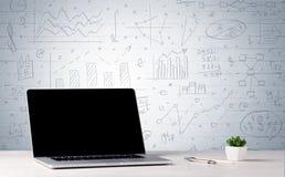 在书桌上的膝上型计算机有在墙壁上的企业图的 图库摄影