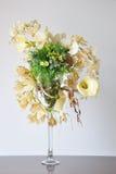 在书桌上的花瓶人造花 免版税图库摄影