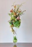 在书桌上的花瓶人造花 免版税库存图片