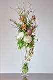 在书桌上的花瓶人造花 库存照片
