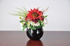 在书桌上的花瓶人造花 免版税库存照片