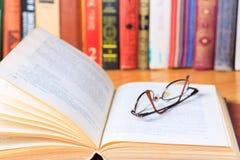 在书桌上的被打开的书在图书馆里 库存图片