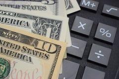 在书桌上计算器和金钱美元 库存图片