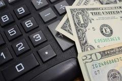在书桌上计算器和金钱美元 免版税库存图片