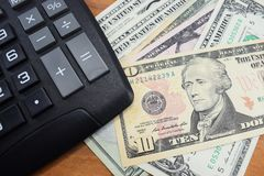 在书桌上计算器和金钱美元 免版税库存照片