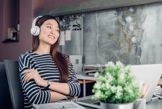 在书桌休息姿势的年轻亚洲偶然女实业家胳膊与lapt 免版税库存照片