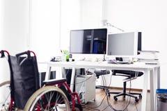 在书桌前面的空的轮椅在现代办公室 免版税库存图片