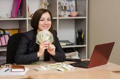 在书桌办公室后的女孩前面的拿着金钱的爱好者他 图库摄影