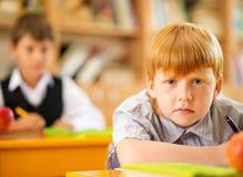 在书桌后的一点红头发人男小学生 库存照片