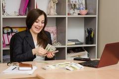 在书桌后的女孩在办公室狂热计数与胜利的微笑的钞票 库存照片