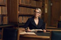 在书桌和阅读书的女性式样开会在图书馆 库存照片