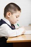在书桌外形视图的白种人男孩文字 免版税库存照片