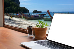 在书桌室外办公室的膝上型计算机和泰国海观看被弄脏的backgrou 免版税库存图片