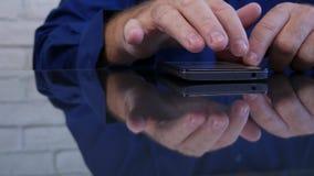 在书桌玻璃表面文本反映的商人图象使用智能手机 股票录像