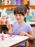 在书桌的女孩绘画在艺术课 免版税库存图片