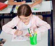 在书桌的女小学生图画在教室 免版税库存图片