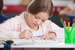 在书桌的女小学生图画 免版税图库摄影