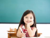 在书桌的小女孩文字在教室 免版税库存图片