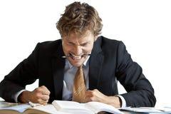 在书桌的恼怒的商人 库存图片