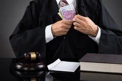 在书桌的法官掩藏的钞票 免版税图库摄影