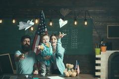 在书桌的美国家庭有与纸飞机的儿子戏剧的 Homeschooling概念 与父母的孩子在有美国的教室 免版税库存照片