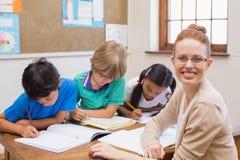 在书桌的老师和学生 免版税库存图片