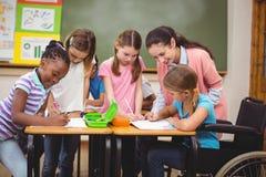 在书桌的老师和学生 免版税库存照片