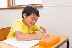 在书桌的逗人喜爱的学生文字在教室 库存照片