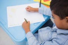 在书桌的逗人喜爱的小男孩图画 免版税图库摄影
