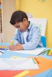 在书桌的逗人喜爱的小男孩图画 库存照片