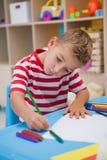 在书桌的逗人喜爱的小男孩图画 库存图片
