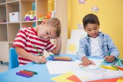 画在书桌的逗人喜爱的小男孩 免版税图库摄影