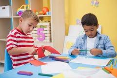 画在书桌的逗人喜爱的小男孩 库存图片
