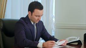 在书桌的年轻商人读书文书工作在办公室和微笑 股票录像