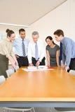 在书桌附近的五个同事 免版税库存图片