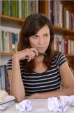 在书桌上的体贴的女学生 免版税库存照片