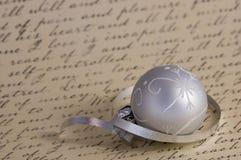 在书法背景的银色圣诞节装饰品 免版税库存图片