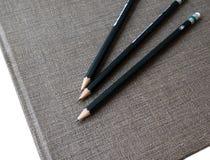 在书的三支铅笔 免版税库存照片