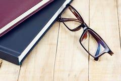 在书的堆的布朗镜片在木工作表上的 免版税库存图片