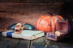 在书的头骨在万圣夜在老葡萄酒木背景的天概念 与拷贝空间的静物画样式增加文本 免版税库存照片