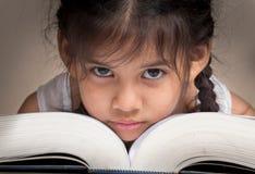 在书的女孩面孔 免版税库存照片