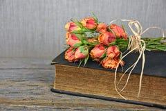在书的桔子玫瑰色花束 免版税图库摄影