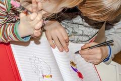 在书的用左手的年轻男孩和姐妹绘画 库存图片