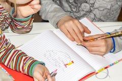 在书的用左手的年轻男孩和姐妹绘画 库存照片