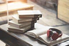 在书的红色耳机在咖啡馆或图书馆 库存图片