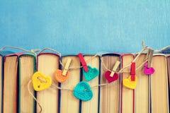 在书的许多多色钩针编织心脏 免版税库存照片
